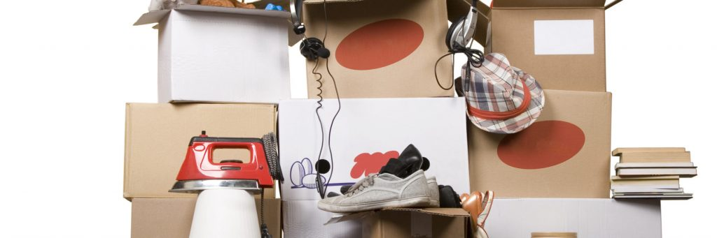 cardboard boxes with books, iron, shoes and clothes